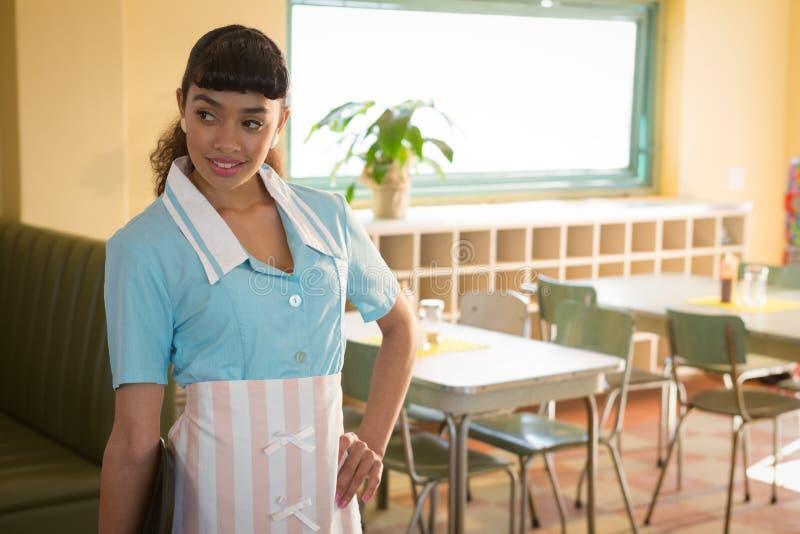 Kelnerki pozycja z rękami na biodrze w restauraci fotografia royalty free
