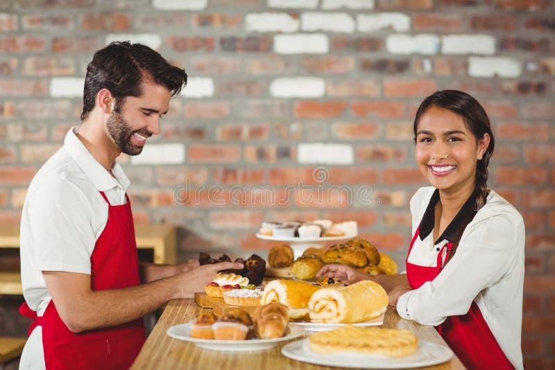 Kelners die gebakjes op de teller opruimen royalty-vrije stock afbeeldingen