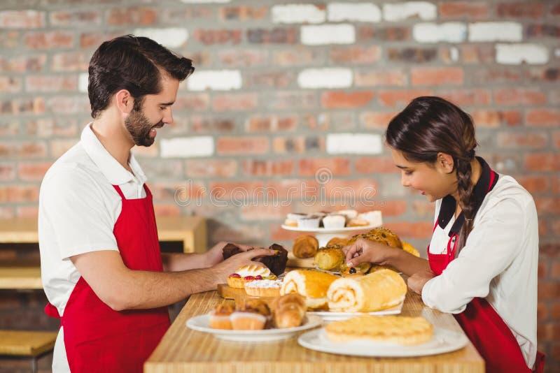 Kelners die gebakjes op de teller opruimen stock afbeelding
