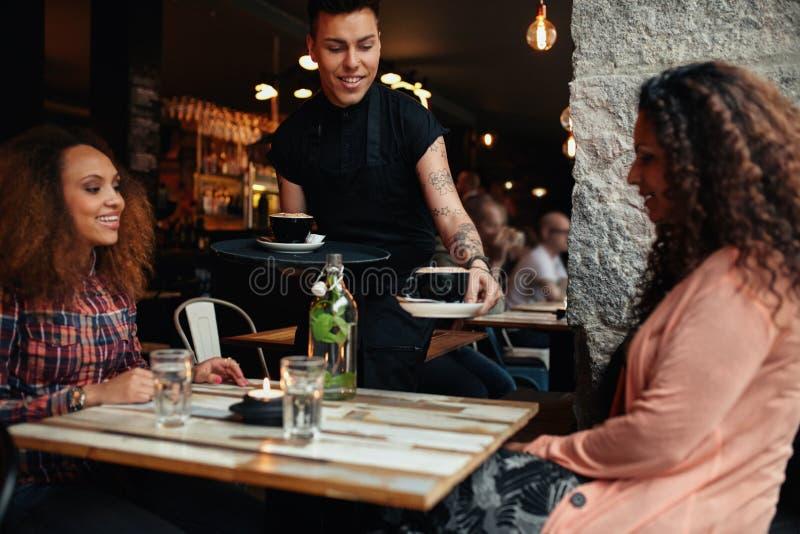 Kelners dienende koffie aan jonge vrouwen bij koffie royalty-vrije stock foto's