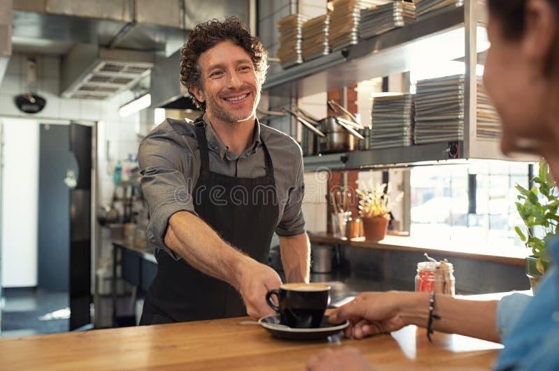 Kelners dienende koffie aan klant stock afbeeldingen