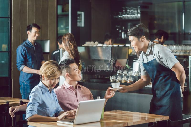 Kelners dienende koffie aan klant stock afbeelding