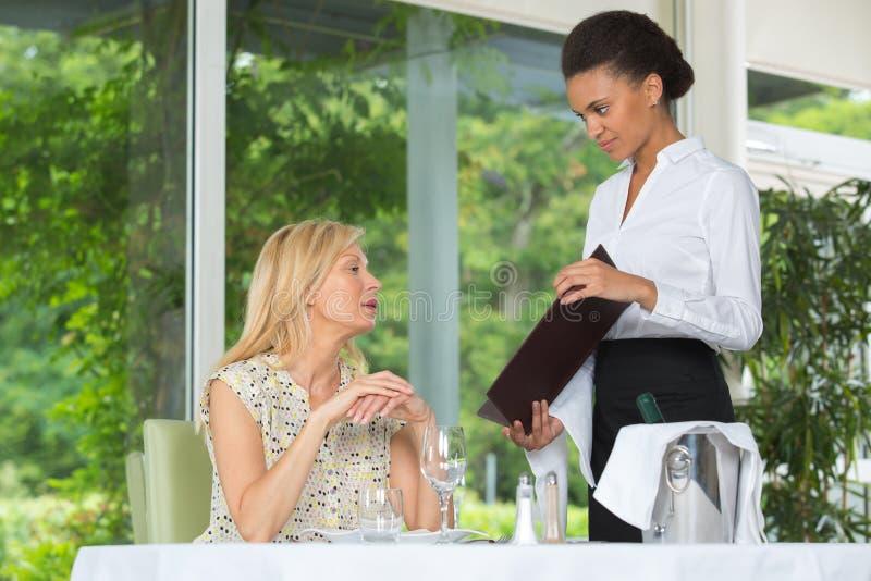 Kelners dienende vrouwen in restaurant stock foto's