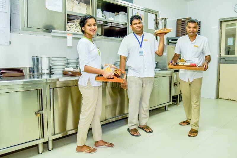 Kelners en serveersterteam in het eenvormige glimlachen met dienbladen in de keuken stock foto