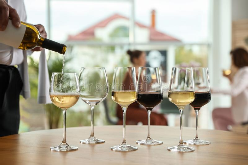Kelners gietende wijn in glas in restaurant, stock foto's