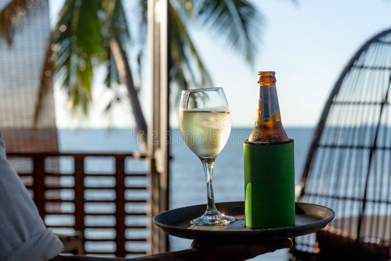 Kelners seaving glas witte wijn en fles bier op een dienblad door het strand stock foto's