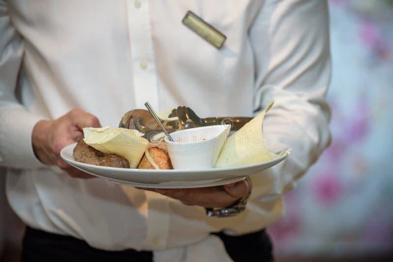 Kelnery niesie talerze z mięsnym naczyniem przy ślubem zdjęcia stock