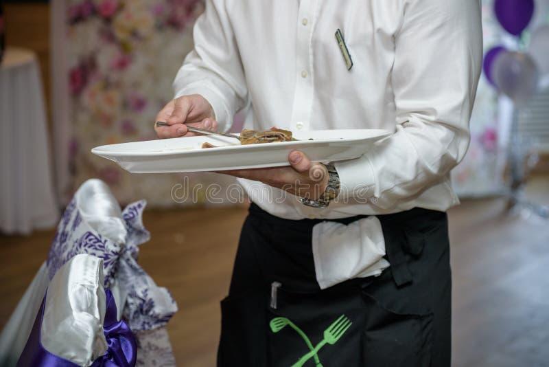 Kelnery niesie talerze z mięsnym naczyniem przy ślubem fotografia royalty free