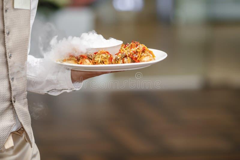 Kelnery niesie talerze z mięsnym naczyniem przy ślubem fotografia stock