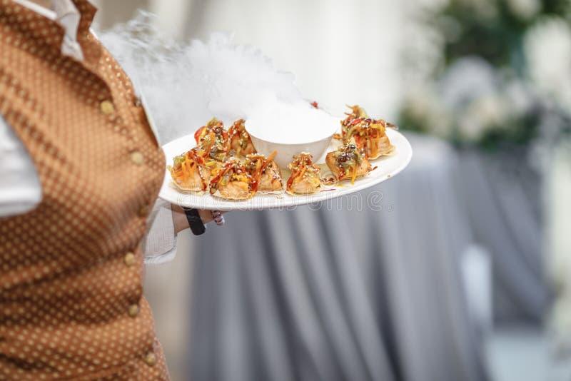Kelnery niesie talerze z mięsnym naczyniem przy ślubem zdjęcia royalty free