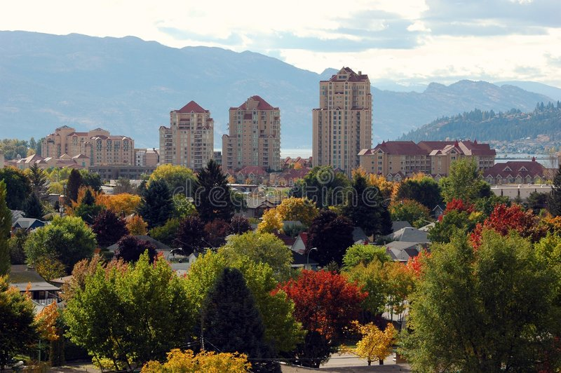 Kelowna in Fall. Vacation rental condos rise over trees with riot of changing autumn leaves in Kelowna British Columbia Canada