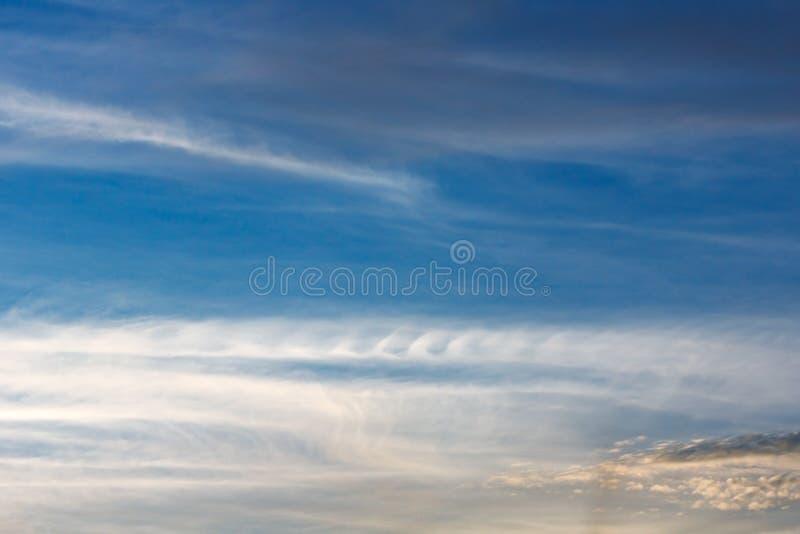 Kelvin Helmholtz ostadighetmoln som är krabba på blå himmel, fjäderlik krullning arkivbild