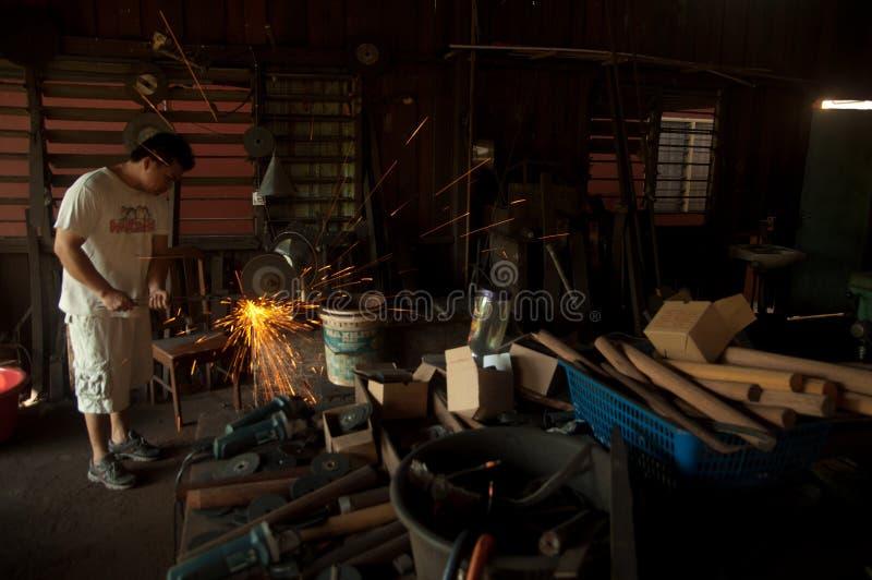 Kemaman, Terengganu, Малайзия - 4-ое апреля 2015 КУЗНЕЦ ДЕЛАЯ НОЖ С ТРАДИЦИОННЫМ ПУТЕМ стоковое фото