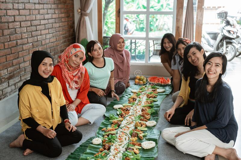 Asian javanese traditional eating together sitting on floor stock photos