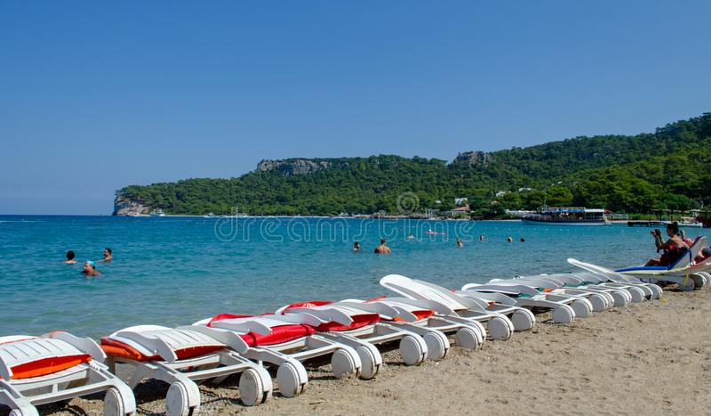 Kemer Antalya Die Türkei - 4. September 2015: leere gefaltete Sonnennichtstuer und -leute, die im Meer baden lizenzfreie stockfotografie