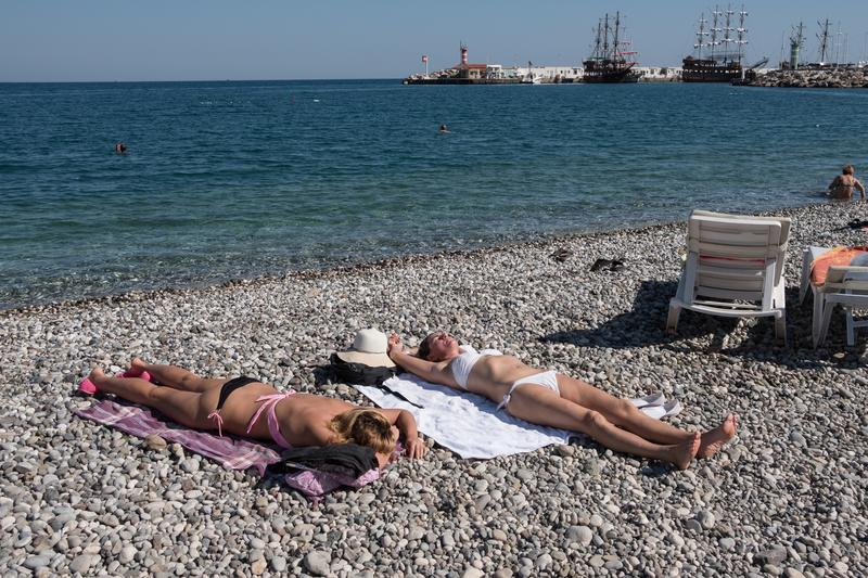 Free beach in a Turkish resort in the town of Kemer. Kemer, Turkey - October 22, 2017: Tourists are resting on the beach of Kemer. two Girls lie on pebbles on royalty free stock photo