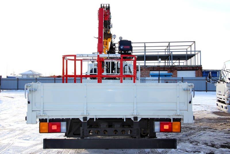 KEMEROVO, RUSIA - 14 DE MAYO DE 2015: gran grúa del camión que se coloca en un emplazamiento de la obra imagen de archivo