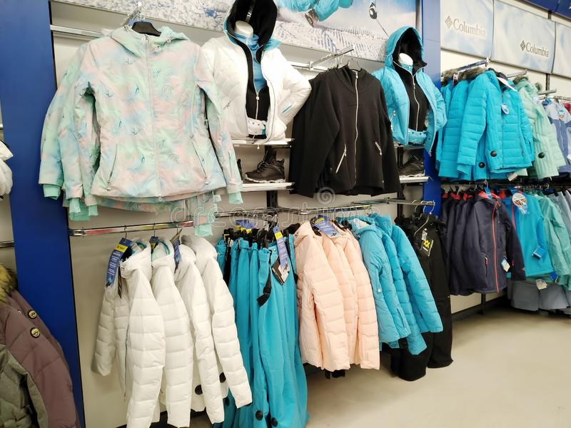 Jackets of various brands for sports activities hang on a hanger in a sports store Sportmaster. KEMEROVO, RUSSIA, NOVEMBER 25, 2018. Jackets of various brands royalty free stock photos