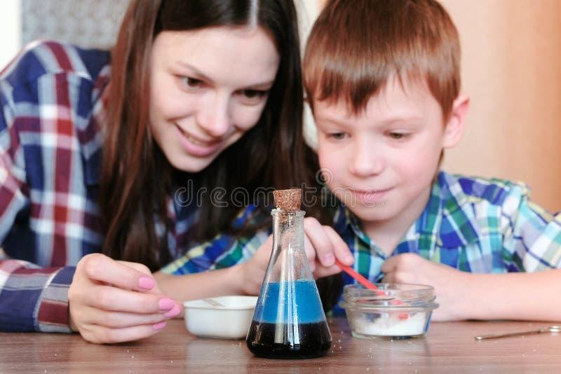 Kemi experimenterar hemma Mamman och sonen gör en kemisk reaktion med frigöraren av gas i flaskan royaltyfri foto