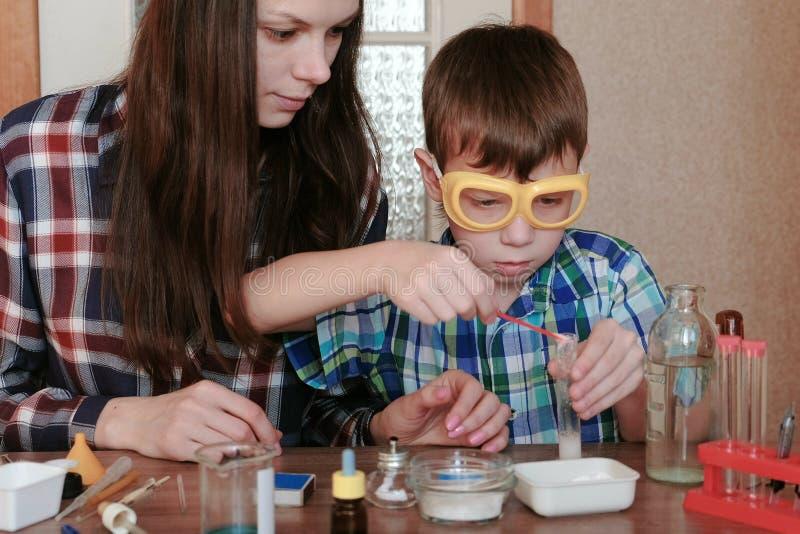 Kemi experimenterar hemma Mamman och sonen gör en kemisk reaktion med frigöraren av gas i provröret royaltyfri fotografi