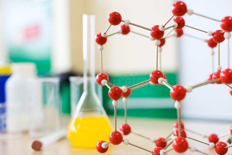 Kemiglasföremål med modellen för vätskeformel och för molekylär struktur på vetenskapsklassrumlaboratoriumet royaltyfri fotografi