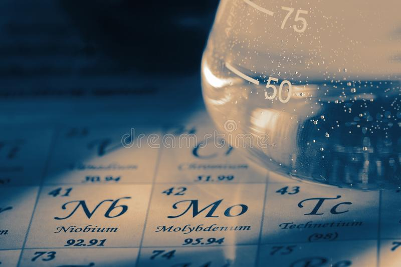 Kemikalieer i exponeringsglaslaboratoriumflaska på diagrammet för periodisk tabell fotografering för bildbyråer