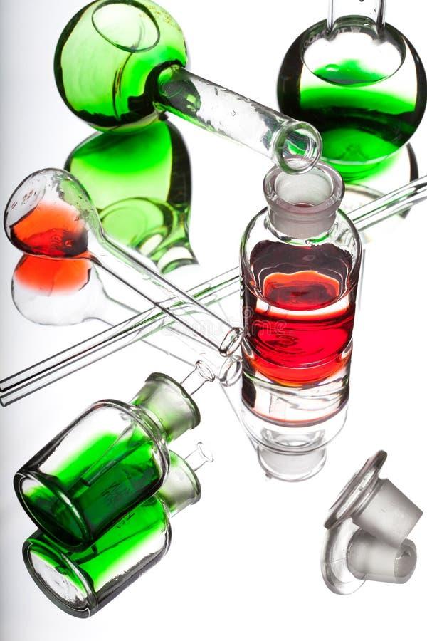 Kemilaboratoriumglasföremål med färgflytande på vitbaksida royaltyfri bild