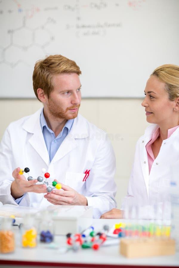 Kemisk professor med den molekylära modellen och assistenter i clen royaltyfri foto