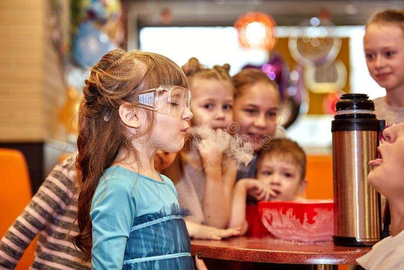 Kemisk show för ungar Professorn bar ut kemiska experiment med vätskegasformigt grundämne på födelsedagliten flicka royaltyfri bild