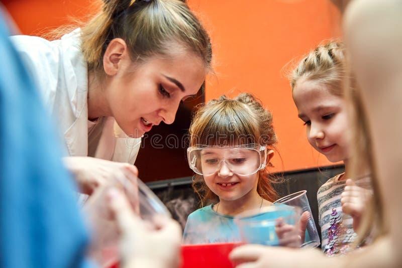 Kemisk show för ungar Professorn bar ut kemiska experiment med vätskegasformigt grundämne på födelsedagliten flicka royaltyfri foto