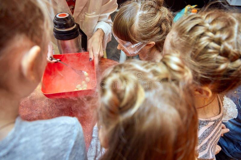 Kemisk show f?r ungar Professorn bar ut kemiska experiment med v?tskegasformigt grund?mne p? f?delsedagliten flicka arkivbild