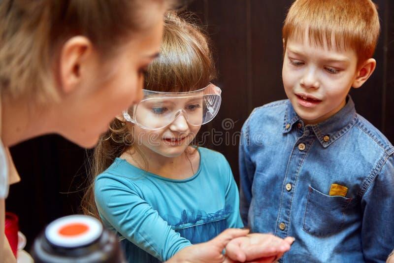 Kemisk show f?r ungar Professorn bar ut kemiska experiment med v?tskegasformigt grund?mne p? f?delsedagliten flicka royaltyfri fotografi