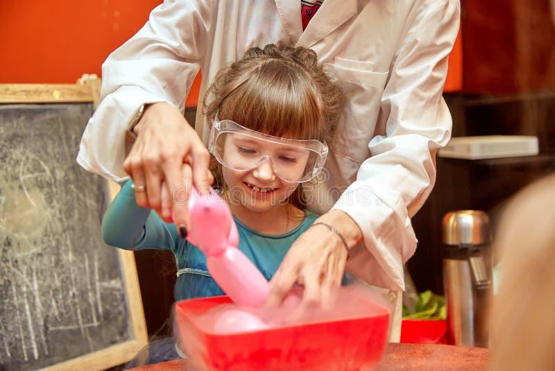 Kemisk show f?r ungar Professorn bar ut kemiska experiment med v?tskegasformigt grund?mne p? f?delsedagliten flicka fotografering för bildbyråer