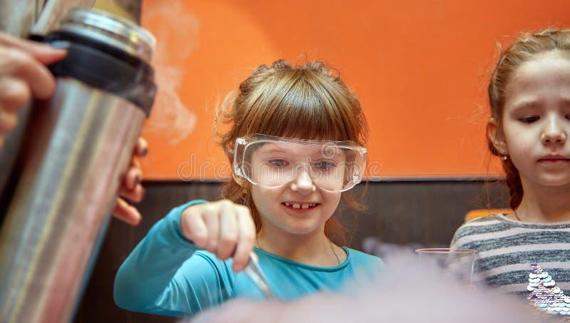 Kemisk show f?r ungar Professorn bar ut kemiska experiment med v?tskegasformigt grund?mne p? f?delsedagliten flicka royaltyfria foton