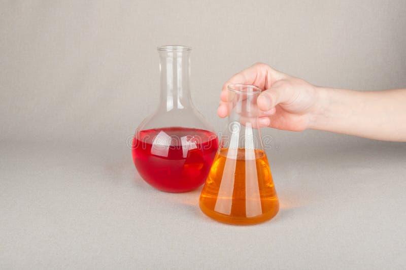 Kemiska flaskor med färgflytande i hand på tabellen arkivbilder