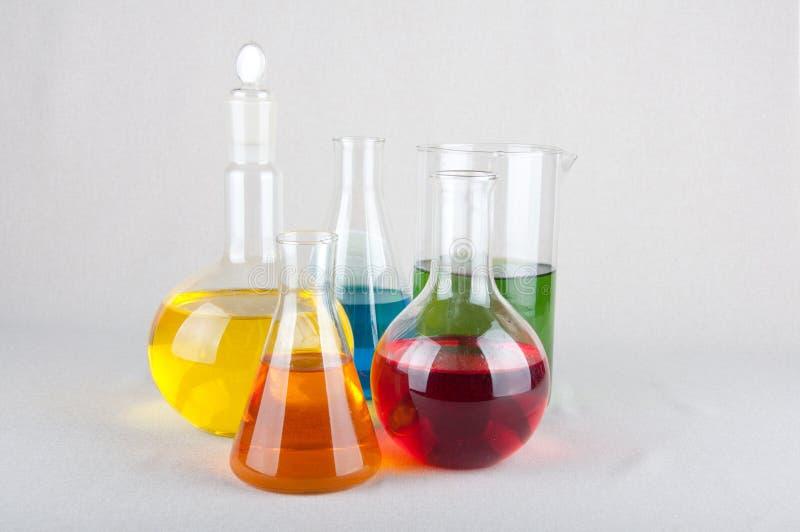 Kemiska flaskor med färgflytande på vit bakgrund royaltyfri bild
