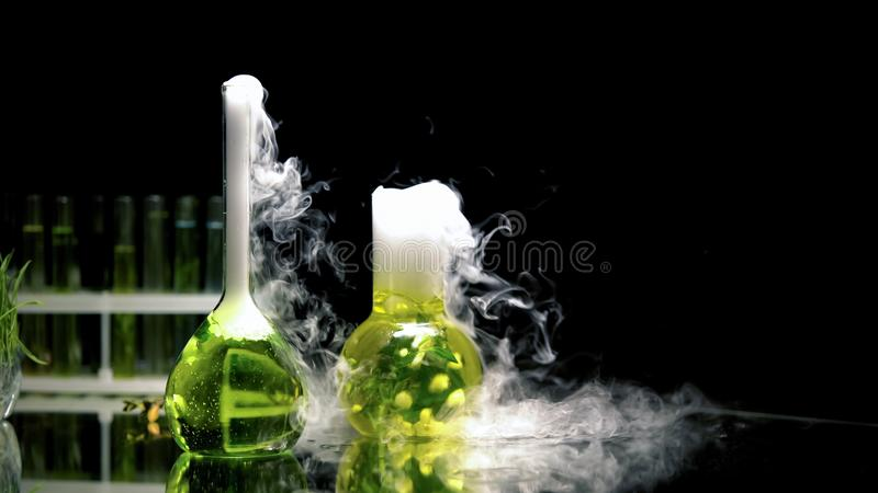 Kemiska flytande i flaskor som bubblar och s?nder ut r?k i m?rker, reaktion royaltyfria foton