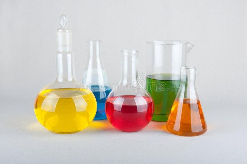 Kemiska glasföremål med färgflytande på vit bakgrund arkivfoton