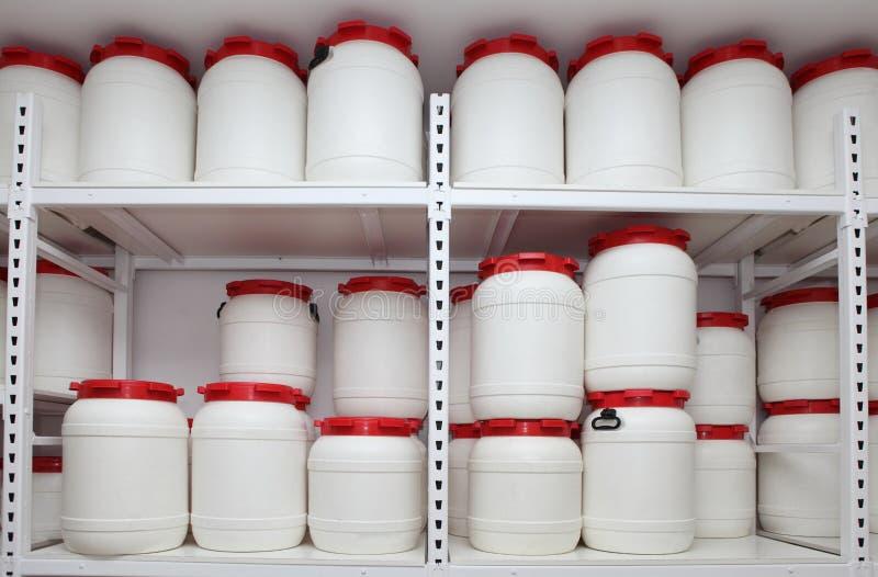 Kemiska plast- trummor på hyllor i magasin royaltyfria foton