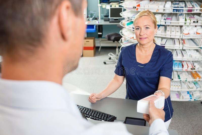 Kemist Giving Medicine Box till den manliga kunden in arkivbilder