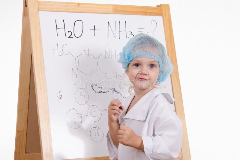 Kemisten skriver formler på en svart tavla arkivbild