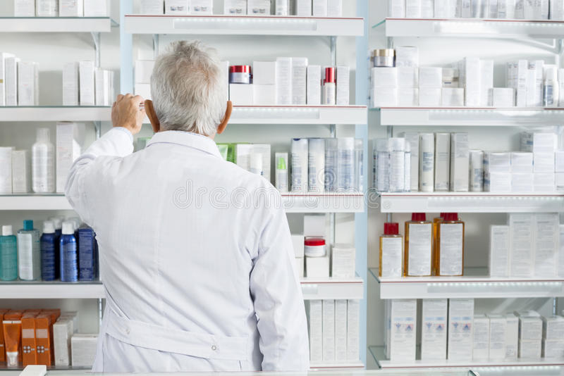KemistSearching Medicines In hyllor på apotek royaltyfri fotografi