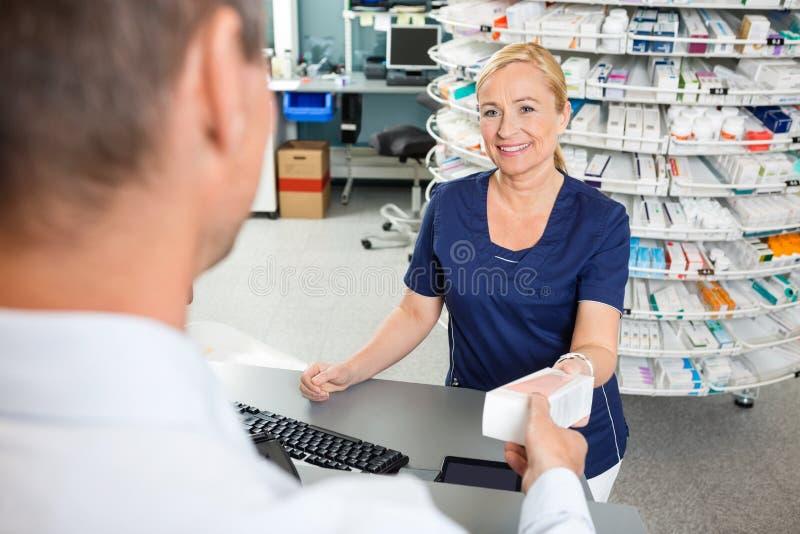KemistSmiling While Giving medicin till kunden royaltyfria foton