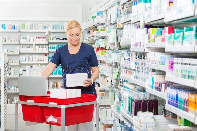 KemistUpdating Stock In bärbar dator på apotek arkivfoton
