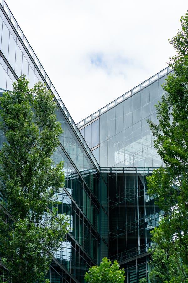 Kemper Platz, Berlin, Deutschland - 7. Juli 2019: moderne Glasfassade eines Gebäudes im Gegensatz zu grünen Bäumen lizenzfreie stockfotos