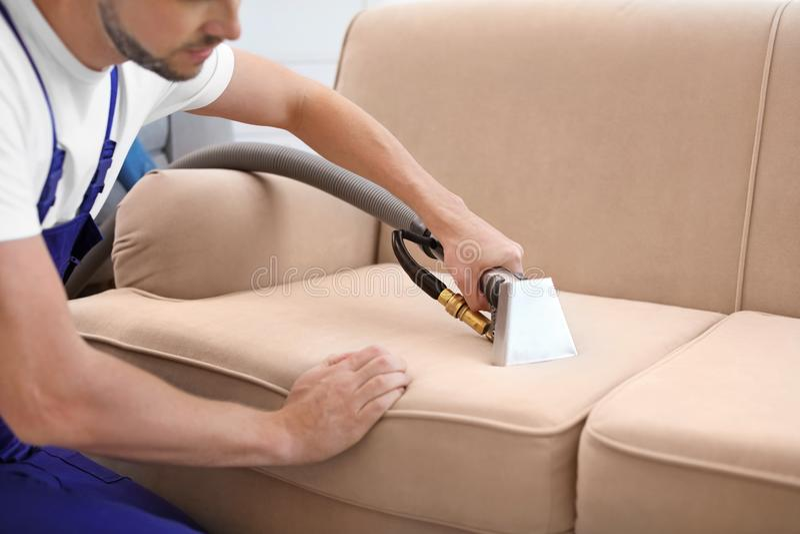 Kemtvättarbetare som tar bort smuts från soffan royaltyfri fotografi