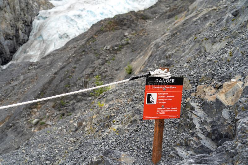 Kenai Fjords National Park - sign warns of dangers for hikers on the Exit Glacier trail in Alaska. Danger sign warns hikers on the Exit Glacier Trail in Kenai stock photography