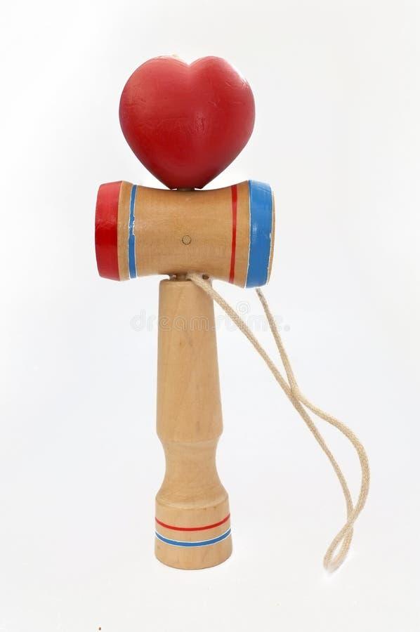 Kendama,包括剑和心脏球的一个传统日本玩具连接由在心形滚动的串,被隔绝 库存图片