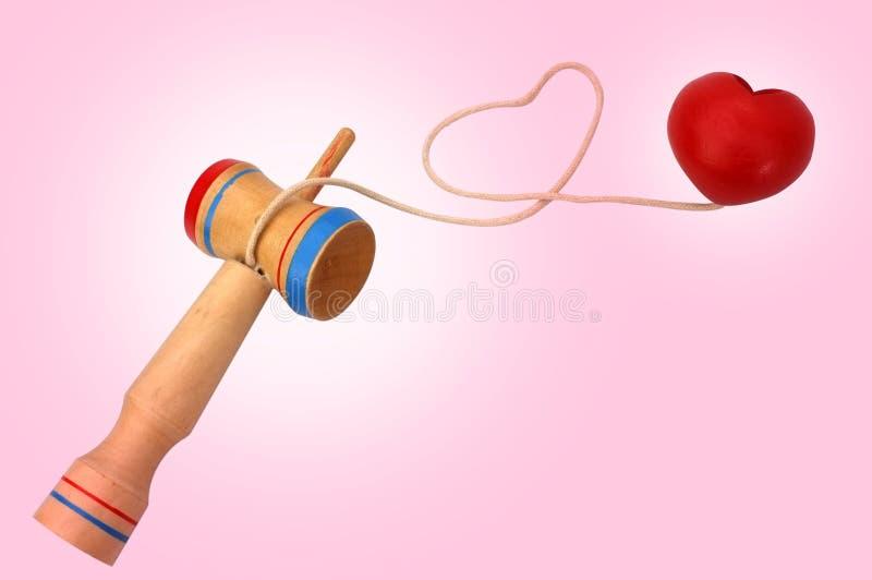 Kendama,包括剑和球的一个传统日本玩具连接由在心形滚动的串,在桃红色 库存图片
