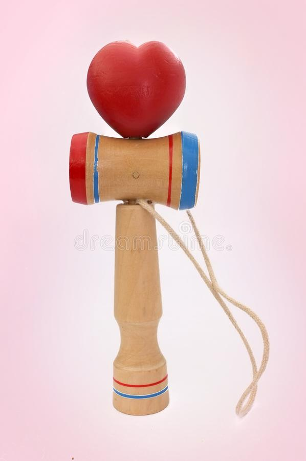 Kendama,包括剑和球的一个传统日本玩具连接由在心形滚动的串,在桃红色 免版税图库摄影